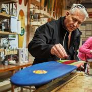 Mechanical engineering alumnus Mike Maloney works on KOTA longboard