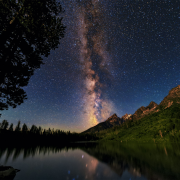 Milky Way over a lake, trees and mountains