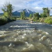 With Colorado's Mount Sopris in the background, water flows along the Roaring Fork River