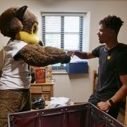 student and Chip in a residence hall during move-in
