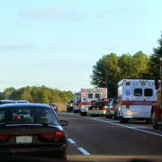 Cars drive past emergency vehicles pulled over in right lane