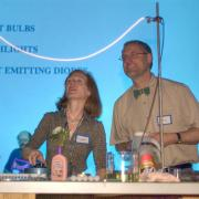 Two faculty members present a electrical light-based experiment.
