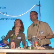 Two faculty members present an electrical light-based experiment.