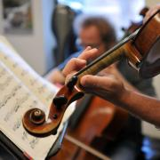 Person playing violin, looking at sheet music