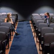 Two students physically distance in an auditorium on campus