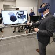 NASA Administrator Jim Bridenstine tries on a virtual reality headset during a tour of CU Boulder's new Aerospace Engineering Sciences Building