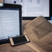 Image of a cell phone, tablet and newspaper