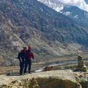 Men standing next to a mountain range.