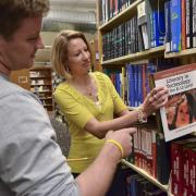 Faculty member pulls a book at Norlin Library