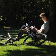 Student sits in grass at Norlin Quad, with bike lying next to him