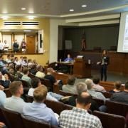 A member pitches to a crowd at a New Venture Challenge event.