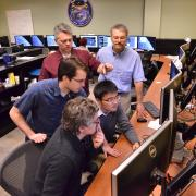 Group huddles around computer monitor