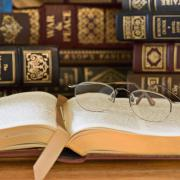 A stock image of old books with a pair of eyeglasses sitting on top of an open page.