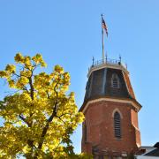 The tower of old main against a blue sky, framed by a branch of yellow leaves.