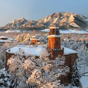 Snowy Old Main tower with American flag overlooking the flatirons