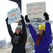 """Protestors display """"Protest the test"""" signs"""