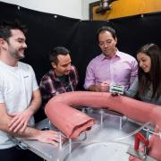 researchers with model of robotic small intestine