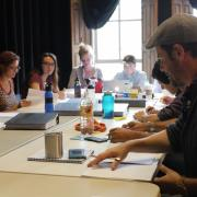 Students and professors participate in a table reading of a modernized version of Henry VI.