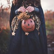 person in black Halloween costume and holding a jack-o-lantern
