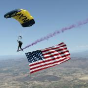 Man parachutes to ground with American Flag