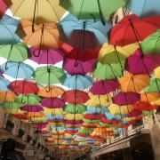 Colorful umbrellas cover a Paris street