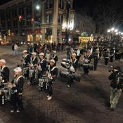 The CU marching band parades down Pearl Street