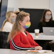 A student wearing a rainbow-colored face mask