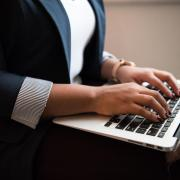 person in business attire working on laptop