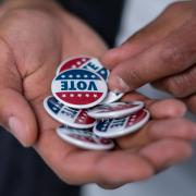 """A person holding """"Vote"""" buttons"""