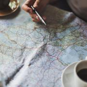People look at map while drinking coffee