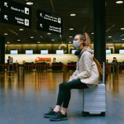 person sitting in airport wearing a mask