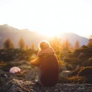 person sitting near campsite alone