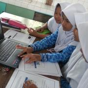 Young students work through PhET simulation on laptop
