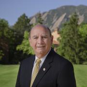 Chancellor Phil DiStefano stands in front of the Flatirons