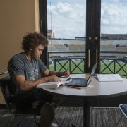 Student-athlete Philip Lindsay studying in club overlooking Folsom Field