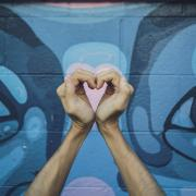 person making a heart with his hands in front of graffiti wall