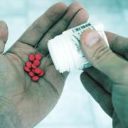 Man pouring pills out of bottle and into hand