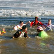 People dressed in tropical wear take a plunge into a frozen body of water