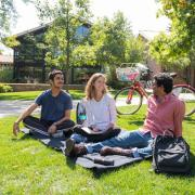 Group of students sitting on the grass at Kittredge Pond smiling