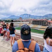Student in CU Buffs hat overlooks Folsom Field