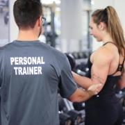 personal trainer works with client in the gym
