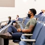 students in a lecture hall, physically distanced and wearing masks