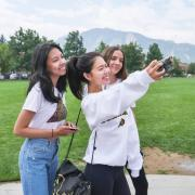 Friends pose for a selfie on campus