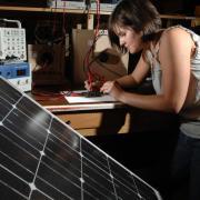 Woman writing electronic engineering proposal