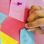 Person pins post-it note on wall