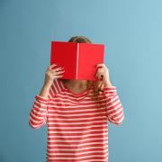 person covering face with red book