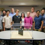 CU Boulder students and faculty display their QB50 micro satellite