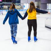 Two women hold hands while ice skating
