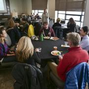 Colleagues sit at tables talking during resource expo