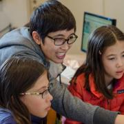 Ricarose Roque works at a computer with young students.